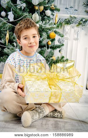 Happy nine year old boy in pajama sitting under the Christmas tree with a gift box and smiling. Christmas concept. Gifts and miracles.