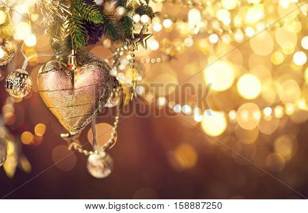 Christmas background, New Year Heart shaped hanging Decoration. Abstract Blurred Holiday Bokeh. Blinking Garland. Christmas Tree Lights Twinkling. Beautiful Winter Holiday backdrop, glowing garlands