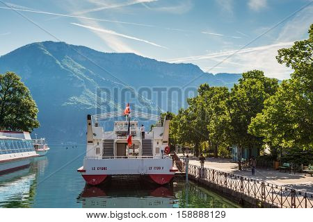 Annecy France - May 25 2016: Tourist excursion boats are moored at the pier seen during the spring sunny day in Annecy Haute Savoie French Alps France. Annecy Lake is one of most popular French resorts. For example a boat trip to discover luxurious landsc