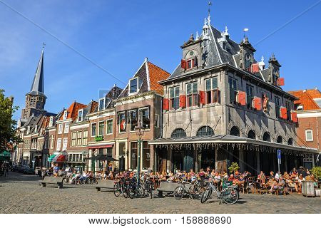 HOORH,NORTH HOLLAND/ THE NETHERLANDS - JUNY 11, 2014: Cafe in the historical building De Waag on the Red Stone square is very popular in summer