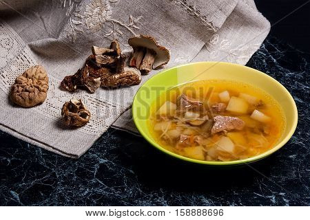Composition With Mushroom Soup In Green Plate, Dried Wild Mushrooms, On A Black Stone Background.