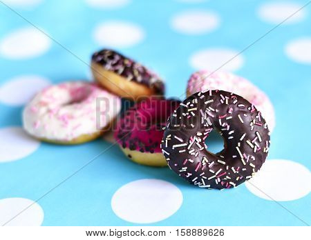 Heap of fresh donuts with glaze on a dots texture. Delicious unhealthy food. Multicolored glazed donuts with chocolate sprinkles.