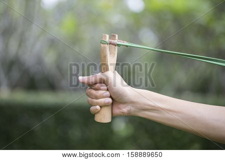 Hand pulling slingshot preparing to shoot a goal business concept