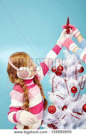 Little red-haired girl putting topper on Christmas tree