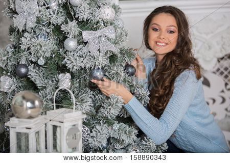 Young beautiful woman decorating Christmas tree at home