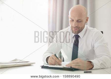 Mid adult businessman writing on clipboard in office