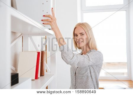 Smiling pretty business woman taking book from a shelf while standing in office and looking at camera