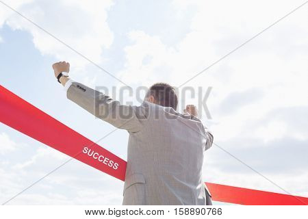Rear view of businessman crossing finish line against sky with text saying success