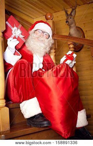 Santa Claus sitting with resents and smiling at camera
