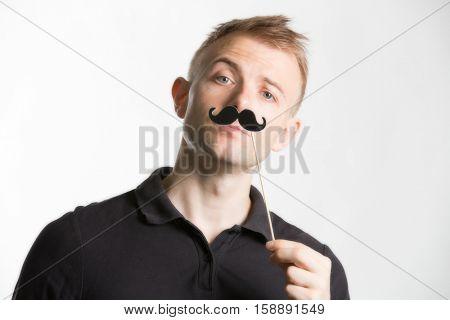 Portrait of an attractive young man wearing a retro style fake moustache
