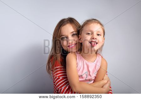 Happy Smiling Mother Hugging With Love Her Frolic Grimacing Kid Showing The Tongue On Blue Backgroun