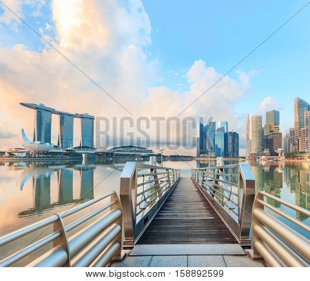 Singapore central quay with pier on foreground. Modern city architecture at sunrise.