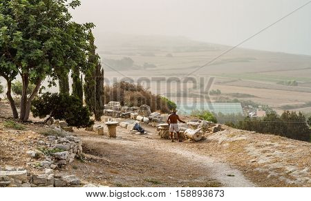 Mediterranean rural landscape in autumn. View from the hill man water the fragments of ancient columns fields and Mediterranean Sea coast in thick mist Cyprus