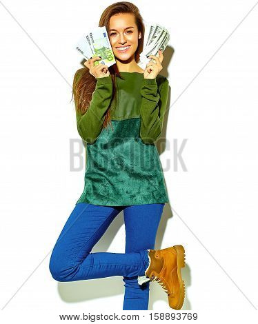 beautiful happy cute smiling brunette woman model in casual green hipster summer clothes with no makeup isolated on white holding dollar and euro banknotes showing her tongue