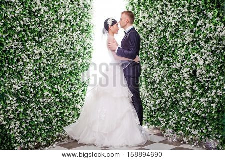 Side view of romantic wedding couple standing amidst flower decorations