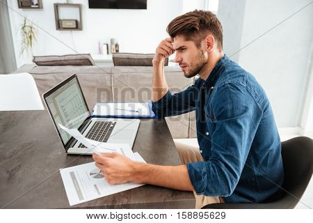 Picture of serious concentrated man working at laptop and sitting at the table while looking at the papers and holding his head with hand.