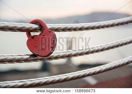 Wedding lock in shape of heart on a handrail. Symbol of marriage.