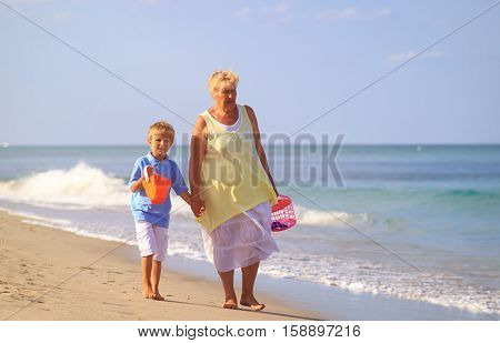 Grandmother and grandson walking at tropical beach, active retirement and family vacation