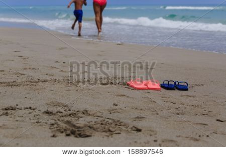 mother and son walking at beach, flip flops on sand, family beach vacation