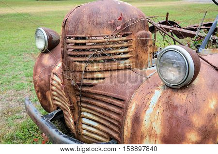 Headlights, bumper and grill of a rusting old truck