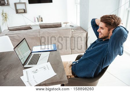 Happy young bristle man sitting at the table with laptop and documents while stretching. Look at the laptop.