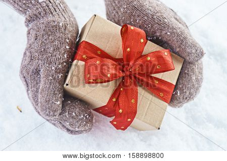 Woman holding Christmas box with gift on light background with snowfall. Hands in woollen gloves holding a nice box with christmas gift. Winter and Christmas time concept.