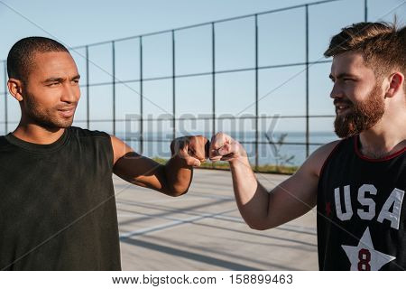 Portrait of a two smiling basketball players fist bumping while standing at the playground