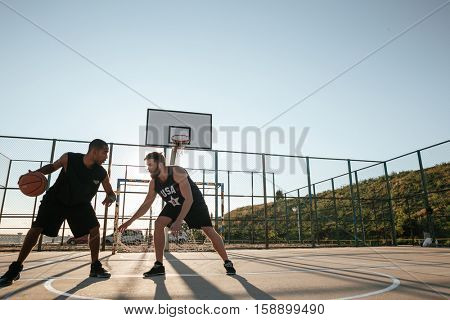 Full length portrait of two sportsmen playing basketball at the playground outdoors