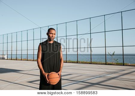 Portrait of a young basketball player standing at the playgroung and holding ball