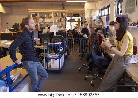 Two Designers Having Informal Meeting In Modern Office