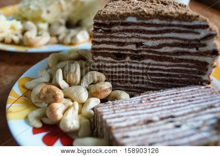 Cake with chocolate shortcakes and white cream on a plate
