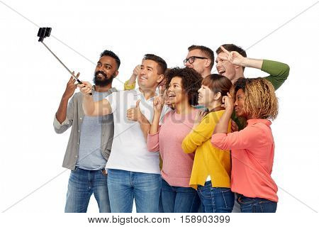 diversity, race, ethnicity, technology and people concept - international group of happy smiling men and women taking picture by smartphone selfie stick over white