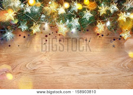 Christmas holiday background. Decorated fir tree with lights on wooden board. Merry Christmas and Happy New Year!! Top view.