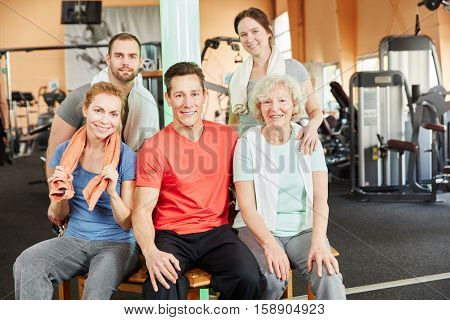Happy oung people group as a team with senior woman at the gym