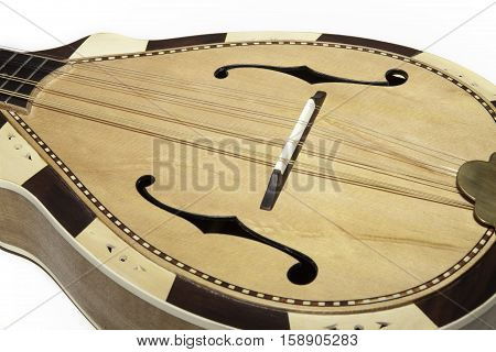 Contemporary acoustic mandolin in traditional style. Eastern style hand-made stringed instrument. Close up of body including f-hole style sound-hole. Shot against white background.