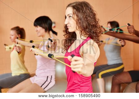 Woman making stretching exercises with expanding band at the gym