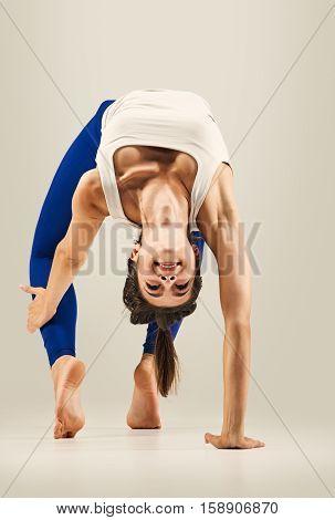 Young woman doing Yoga exercises. studio. Bridge pose - Urdhva Dhanurasana