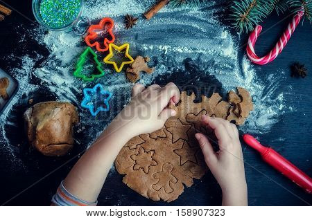 Little girl's hand making traditional Christmas cookies. Raw dough and cutters for the holiday cookies on a dark table. Preparing Christmas gingerbread cookies. Steps of making biscuits. Top view.