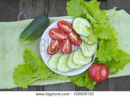 Sliced cucumbers and tomatoes with lettuce on old wooden table.