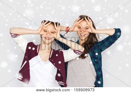 winter, christmas, people, teens and friendship concept - happy smiling pretty teenage girls or friends having fun and making faces over gray background and snow