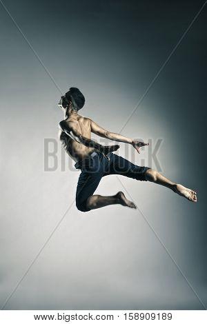 Caucasian man gymnastic leap posture on grey background