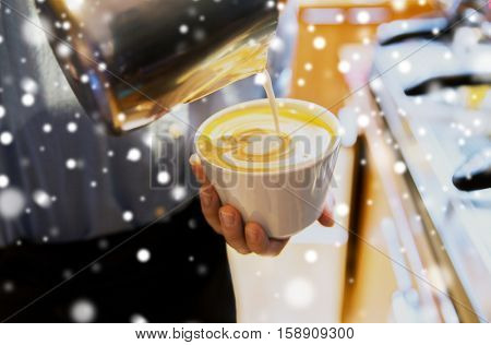 latte art, people and winter holidays concept - close up of woman pouring cream to cup of coffee at cafe bar or restaurant kitchen over snow