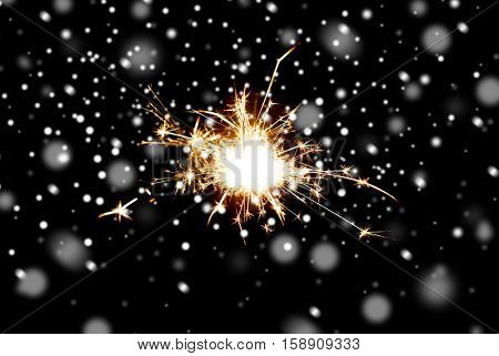 christmas, holidays, new year party and pyrotechnics concept - sparkler or bengal light burning over black background with snow