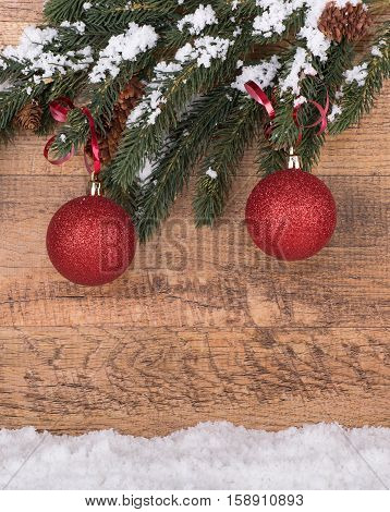 Red Christmas ornaments hanging from a tree branch on a wood background