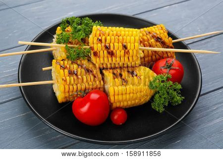Black plate with grilled corncobs, tomatoes and parsley on grey wooden table
