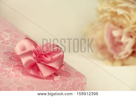 Pink lace gift box with an ivory peony in the background