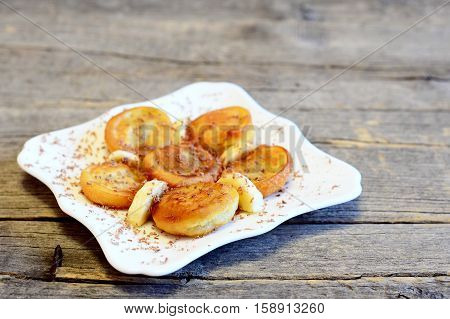 Fried battered banana decorated with chocolate and fresh sliced bananas. Simple delicious fried bananas in batter on a plate isolated on old wooden background. Tasty and healthy breakfast idea