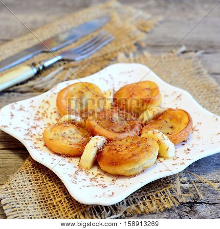 Fried banana fritters decorated with chocolate and fresh sliced bananas. Easy delicious fried bananas in batter on a plate, fork, knife, burlap on wooden table. Vegetarian breakfast recipe. Closeup