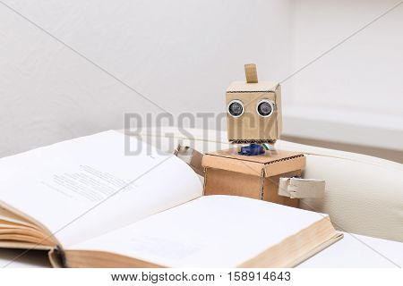 robot reading a book sitting at the table