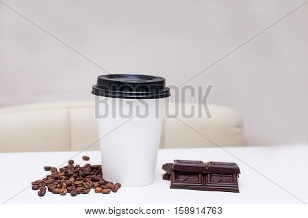 paper cup with chocolate chips and coffee beans